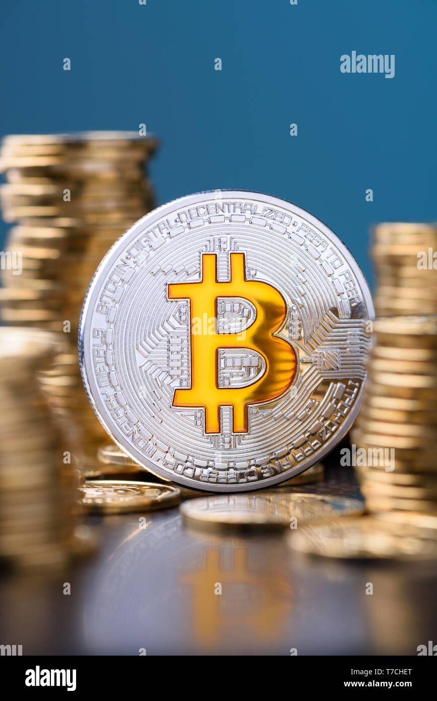 Bitcoin. Bitcoin coin bit golden bit sybmol logo with gold coins stacks vertical on blue background with reflection. - Stock Image