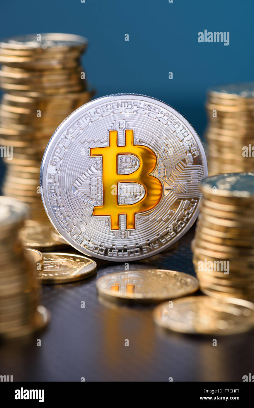 Bitcoin. Bitcoin coin with golden bit sybmol logo and gold coins stacks vertical on blue background with reflection. - Stock Image
