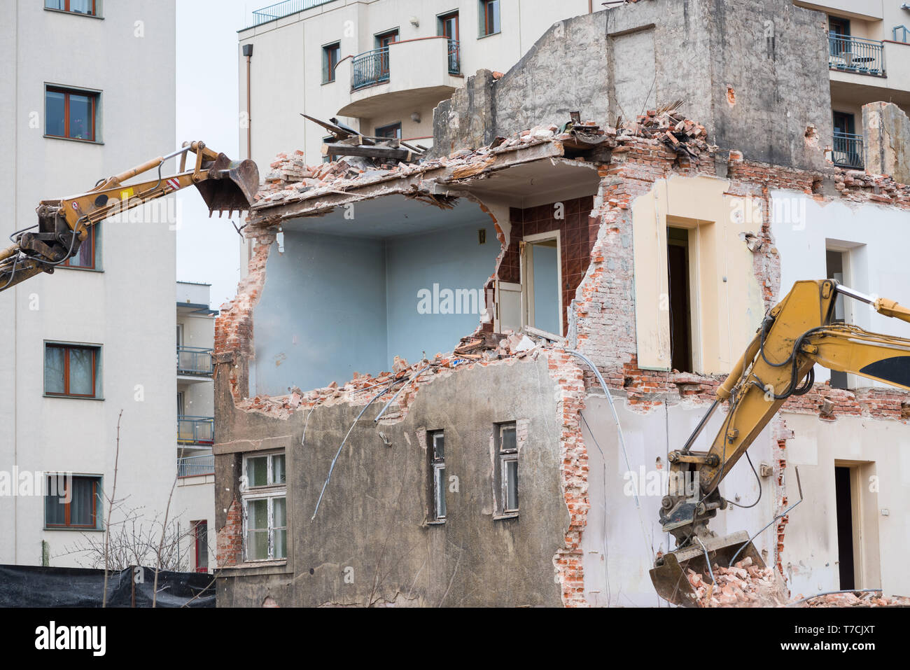Old residential three story building demolition with hydraulic excavators - Stock Image