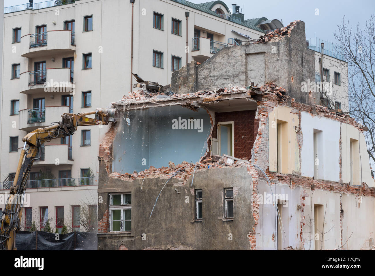 Residential building demolition with excavator - Stock Image