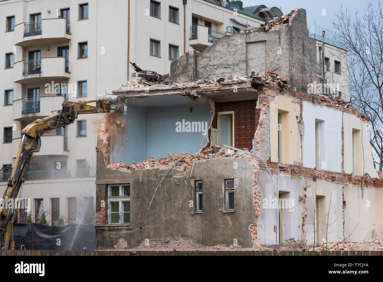 Old residential three story building demolition with excavator - Stock Image