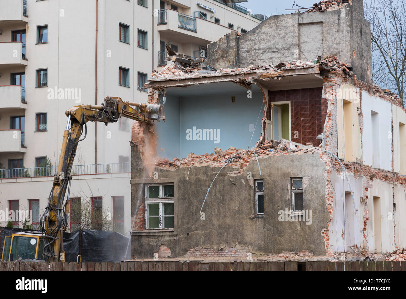 Old residential building demolition with excavator - Stock Image