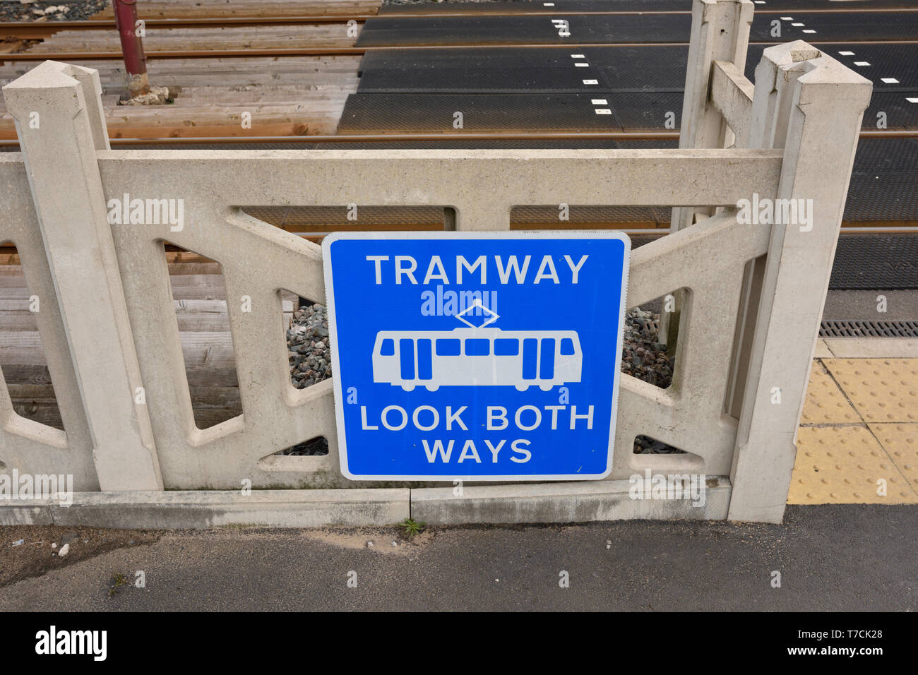 Tramway look both ways warning sign mounted on concrete fence on Blackpol and Fleetwood tramway on the fylde coast in lancashire uk - Stock Image