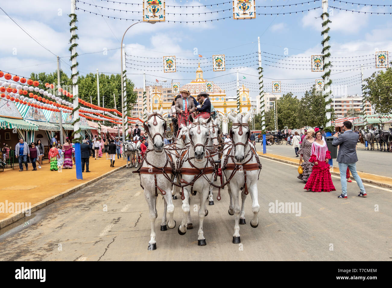 Seville, Spain - May 5, 2019: People entering on horse drawn carriage to the April Fair by main door of the Fair of Seville on May, 5, 2019 in Seville - Stock Image
