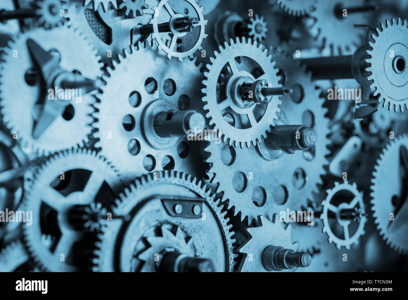 Gears and cogs macro in vintage old mechanism blue toned - Stock Image