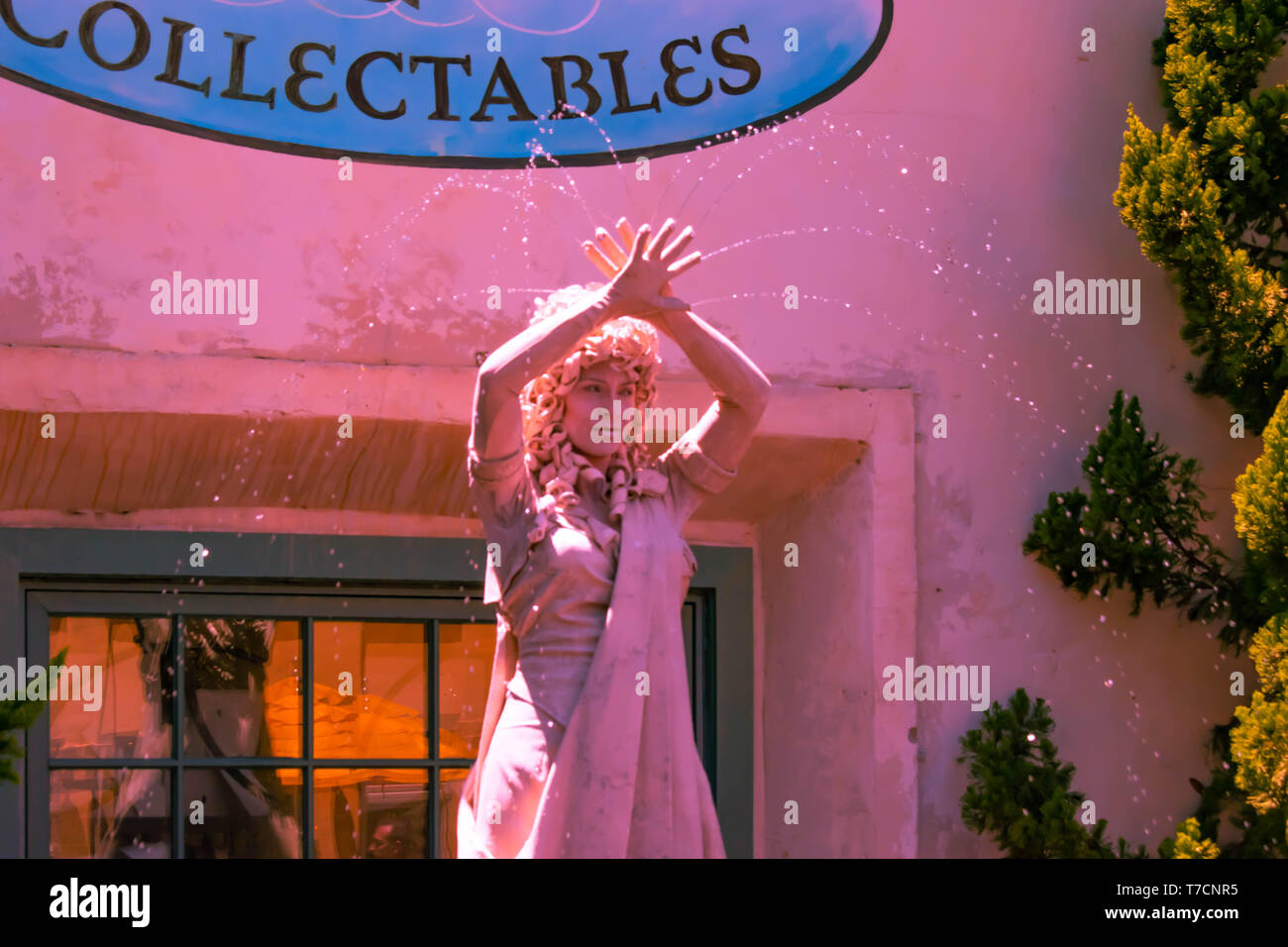 Orlando, Florida. April 20, 2019. Woman living statue throws small jets of water from her hands at Seaworld in International Drive area (1) - Stock Image