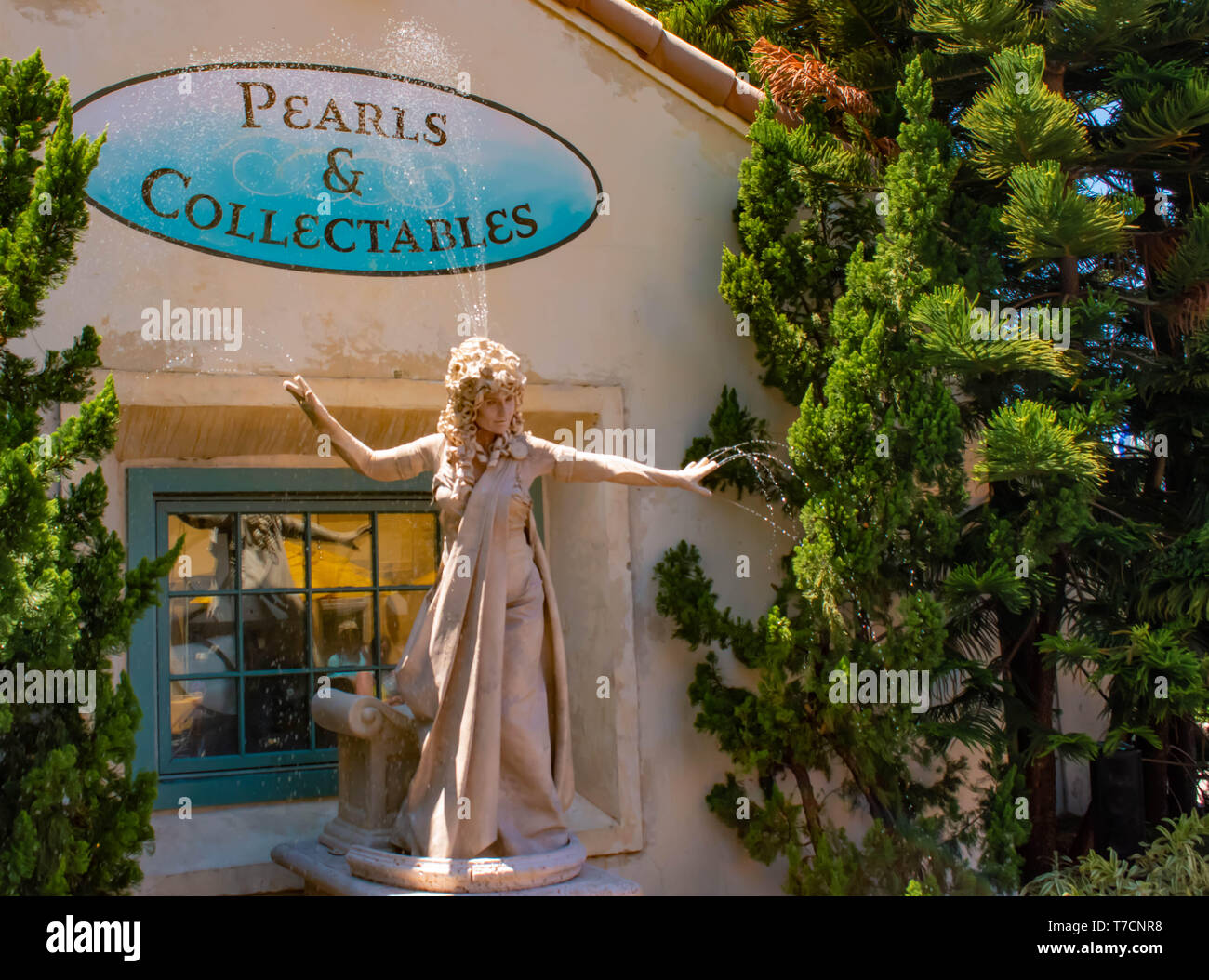 Orlando, Florida. April 20, 2019. Woman living statue throws small jets of water from her hands at Seaworld in International Drive area (2) - Stock Image