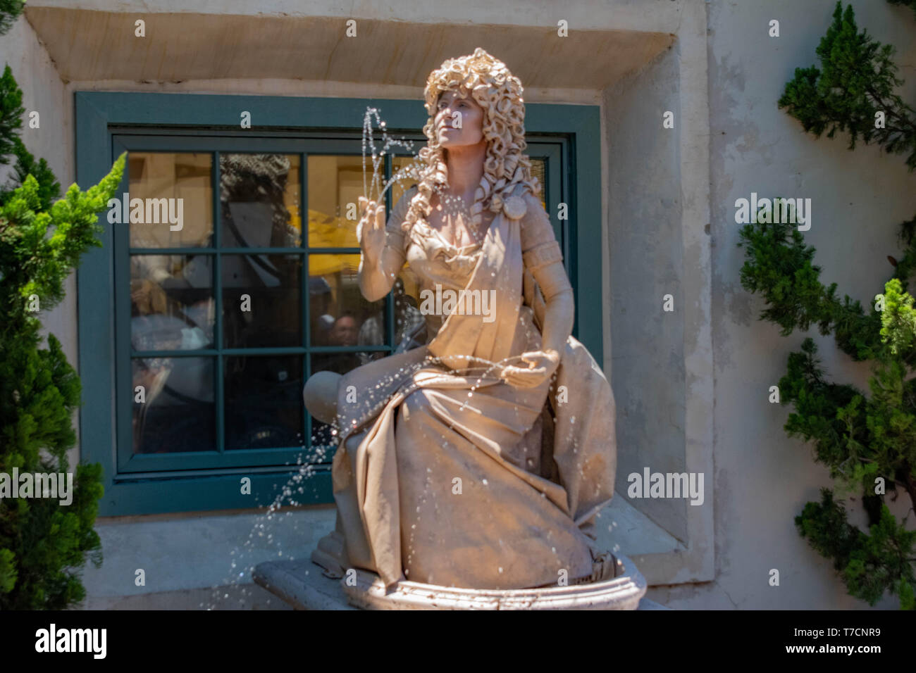 Orlando, Florida. April 20, 2019. Woman living statue throws small jets of water from her hands at Seaworld in International Drive area (3) - Stock Image