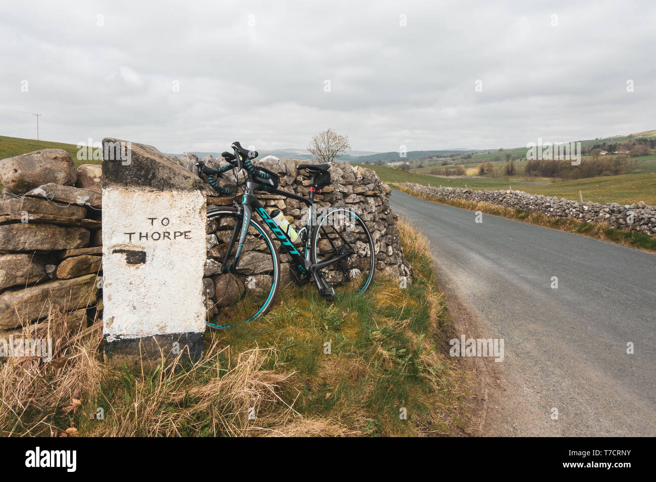Quaint signpost to Thorpe with a pointing finger and a road bike leaned up next to it, Yorkshire Dales, UK - Stock Image