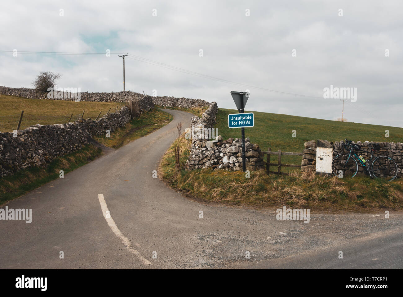 Steep narrow country lane with a quirky signpost to Thorpe, bicycle and unsuitable for HGVs signpost, Yorkshire Dales, UK - Stock Image