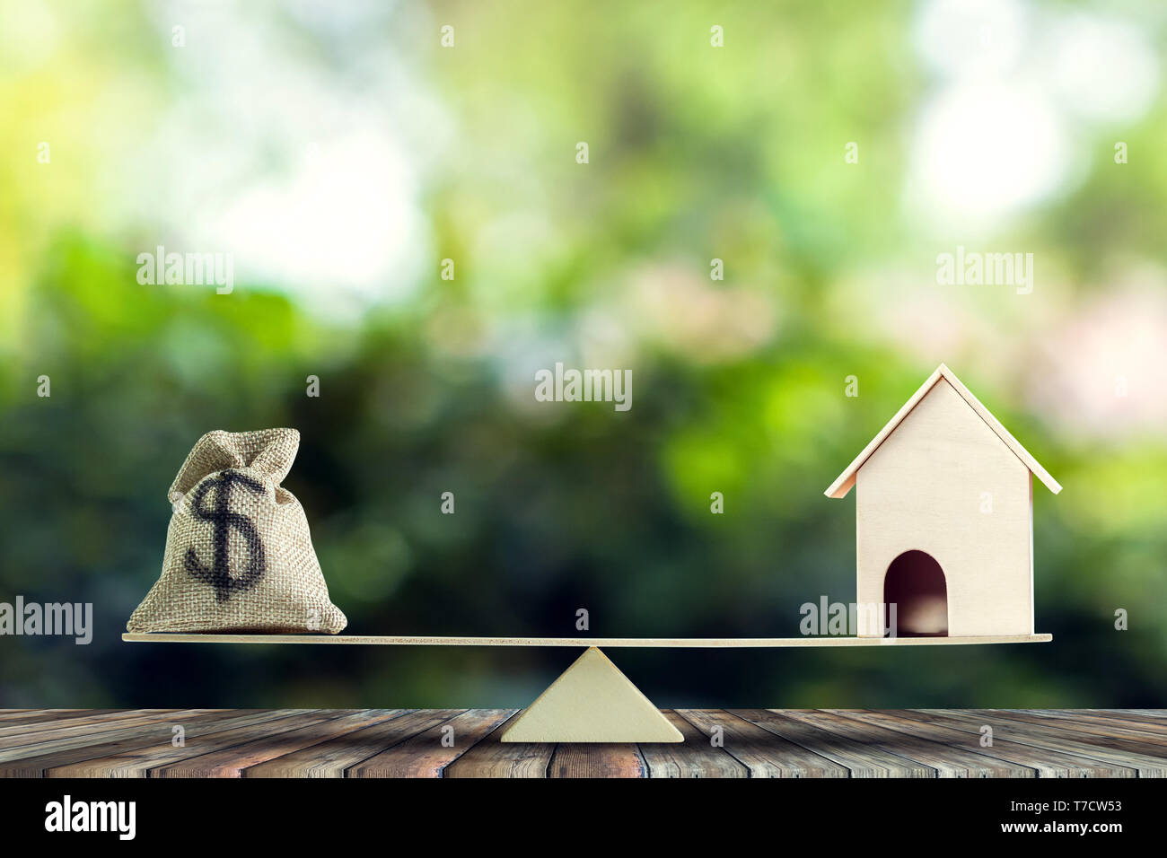 Money and home,loan,mortgage. Change home into cash concept. US Dollar in sack bag, Wooden house model put on scales on wood table with green tree bok - Stock Image