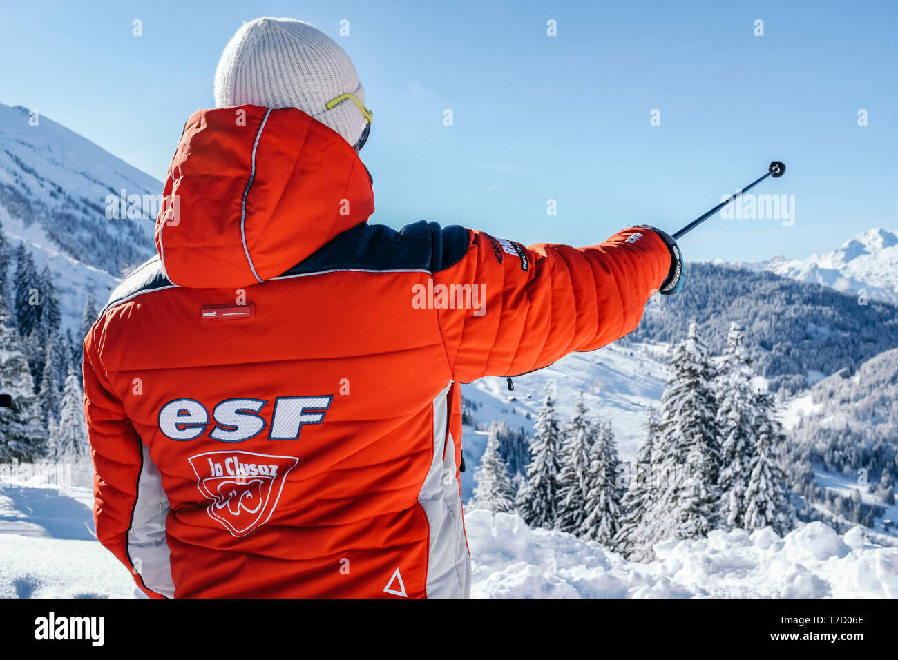 French ski school ESF ski instructor, ski resort of La Clusaz (central-eastern France). Ski instructor pointing out a direction with a ski pole - Stock Image