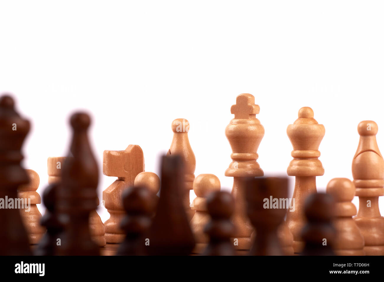 Wooden chess pieces in a duel on a chessboard. King, lady and shooter with horse. Out of focus team of enemies. Isolated on white background - Stock Image