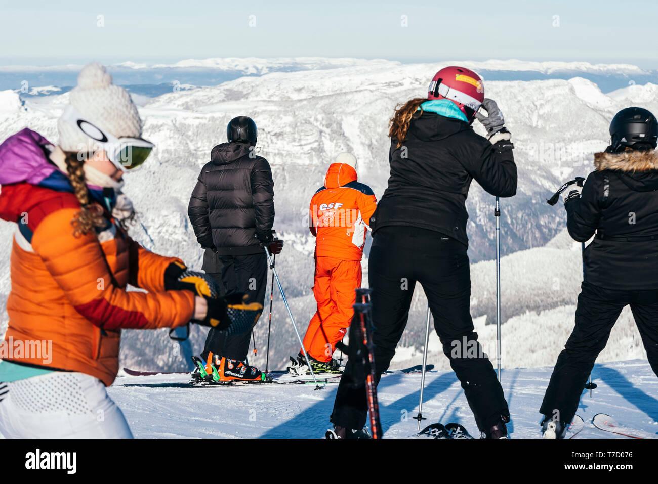 French ski school ESF ski instructor, ski resort of La Clusaz (central-eastern France). Ski instructor and learners atop a ski run Stock Photo