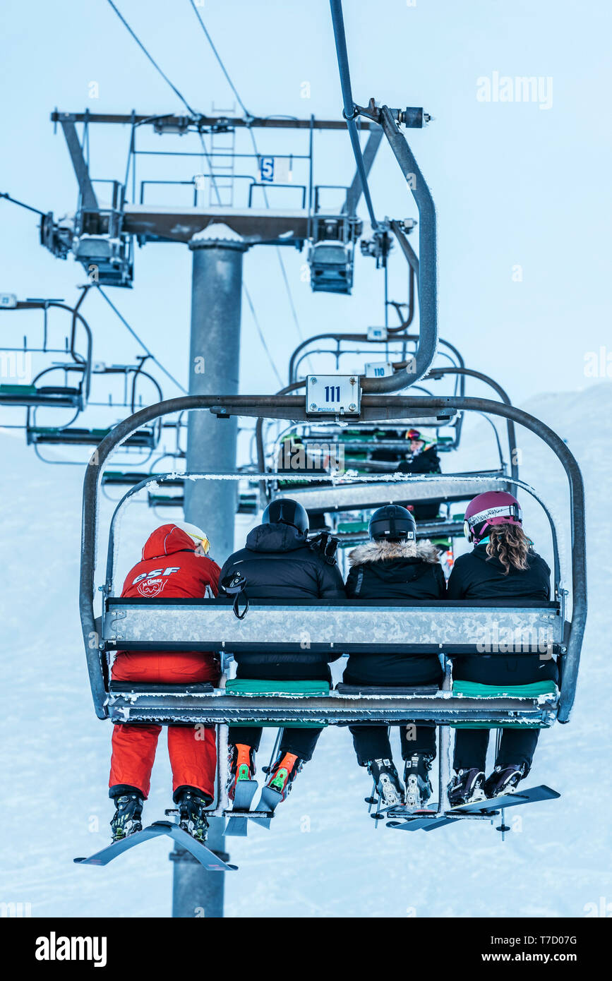 French ski school ESF ski instructor, ski resort of La Clusaz (central-eastern France). Ski instructor and learners sitting on a chairlift - Stock Image