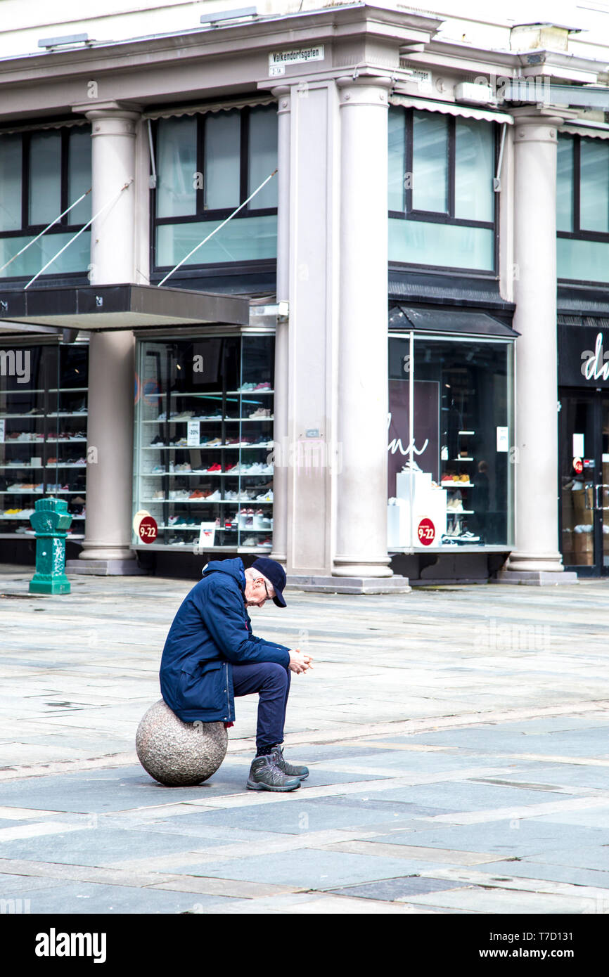 Sad lonely man sitting on a ball in a city Stock Photo