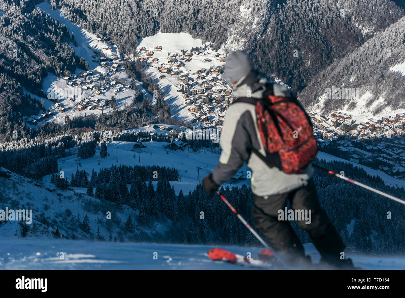 La Clusaz (eastern France): the village covered in snow viewed from the upper ski resort and back view of a skier - Stock Image