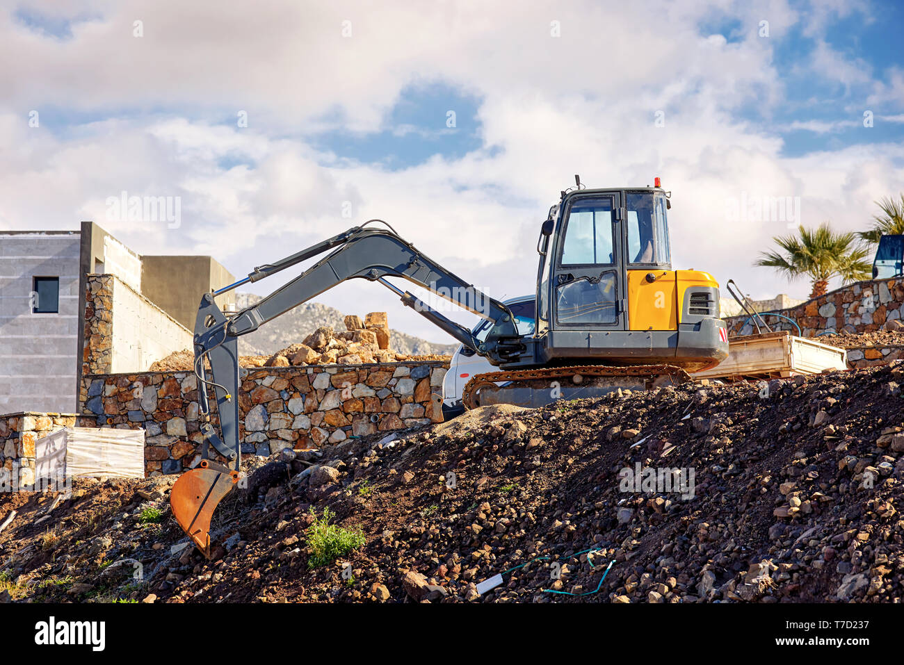Earth mover excavator parked over the hill at a real estate building construction site - Stock Image