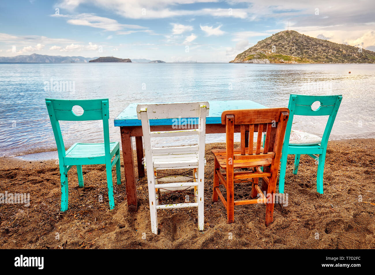 Colorful Retro Wooden Chairs And A Table Lined Up On The Beach At The Seaside In Gumusluk Bodrum Turkey Stock Photo Alamy
