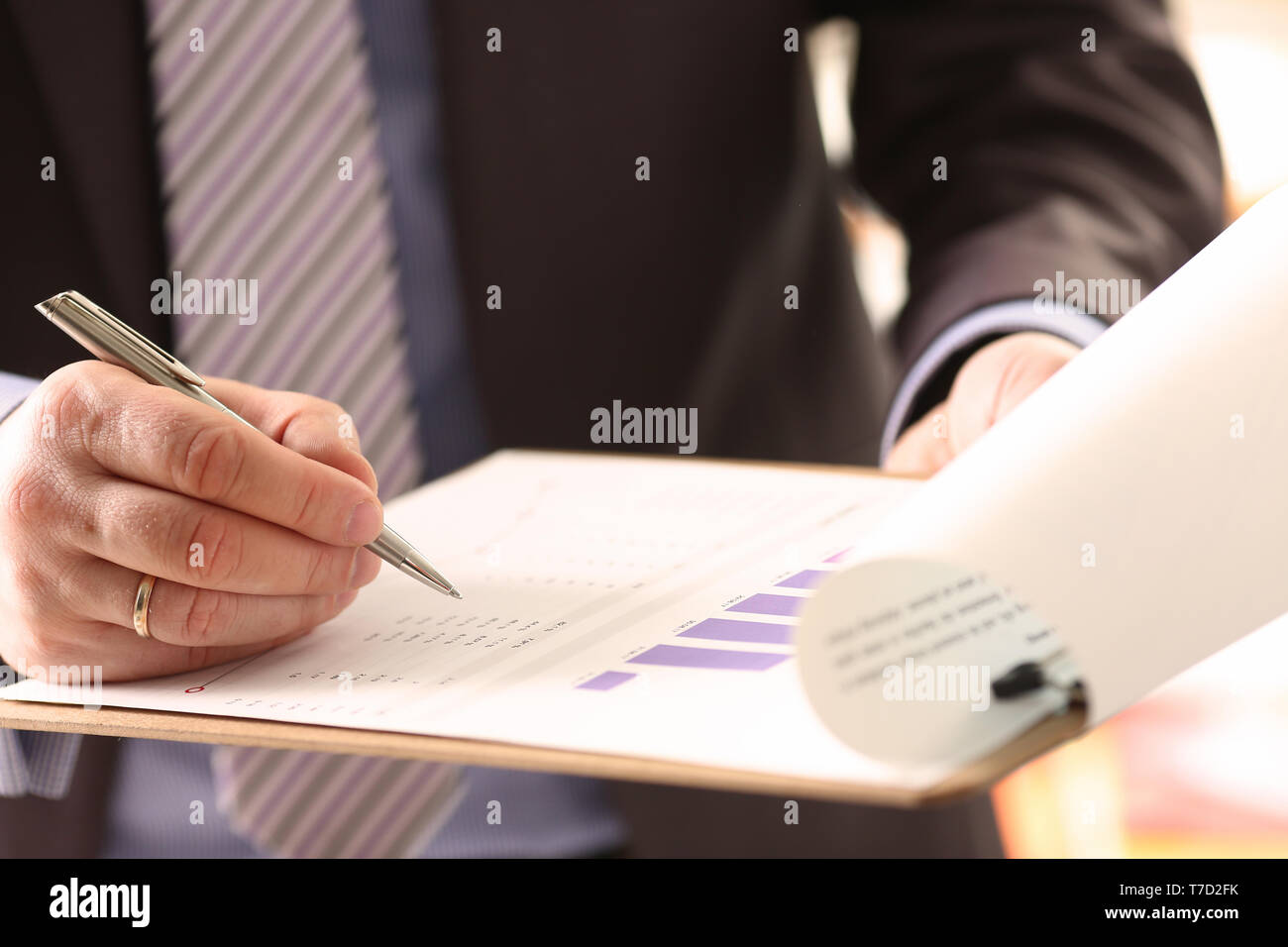 Financial Auditor Signing Calculating Document - Stock Image