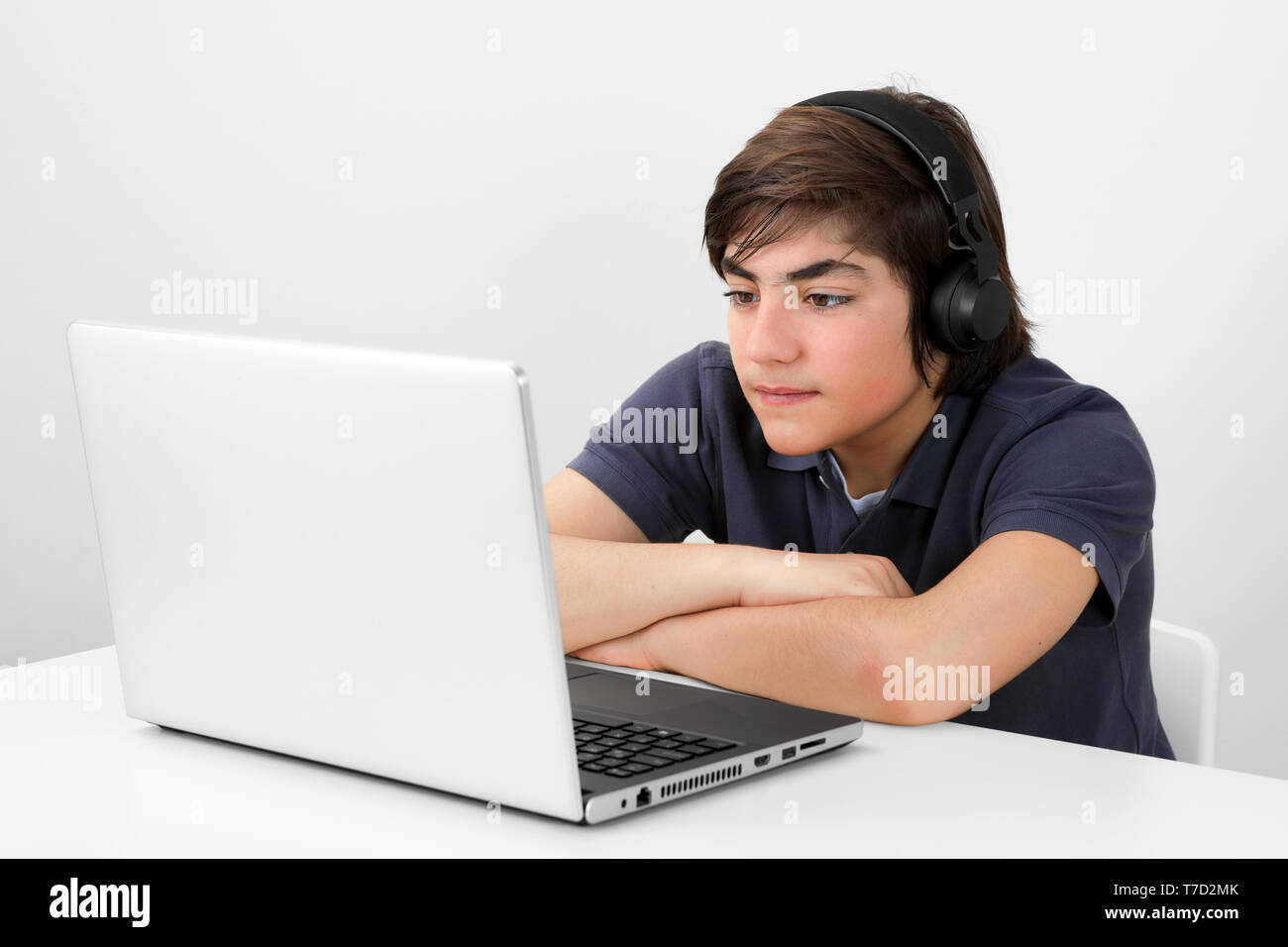 Caucasian teenage boy with headphones sitting at the table and  watching a video at his laptop screen - Stock Image
