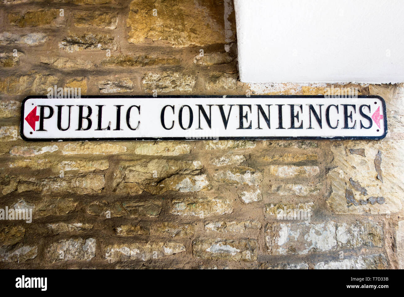 Sign pointing the way to the public conveniences UK - Stock Image
