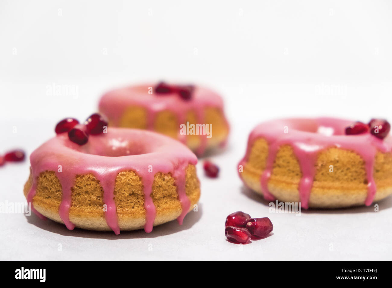 Golden Doughnuts with Dripping Pink Pomegranate Glaze and Fresh Pomegranate Seeds - Stock Image