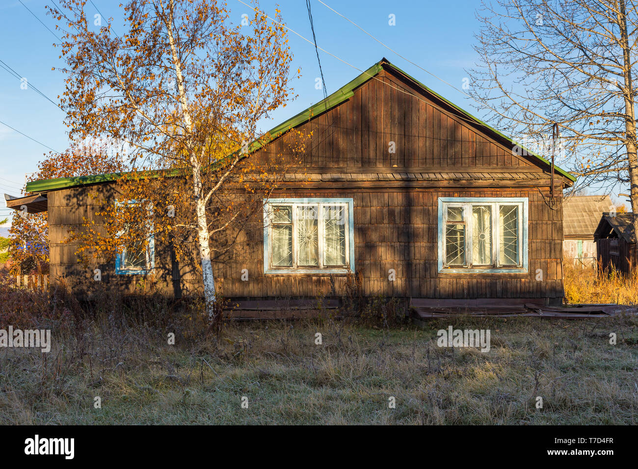 Wooden, rura house in Kozyriewsk on the Kamchatka Peninsula. Tree in the front. Russia. - Stock Image
