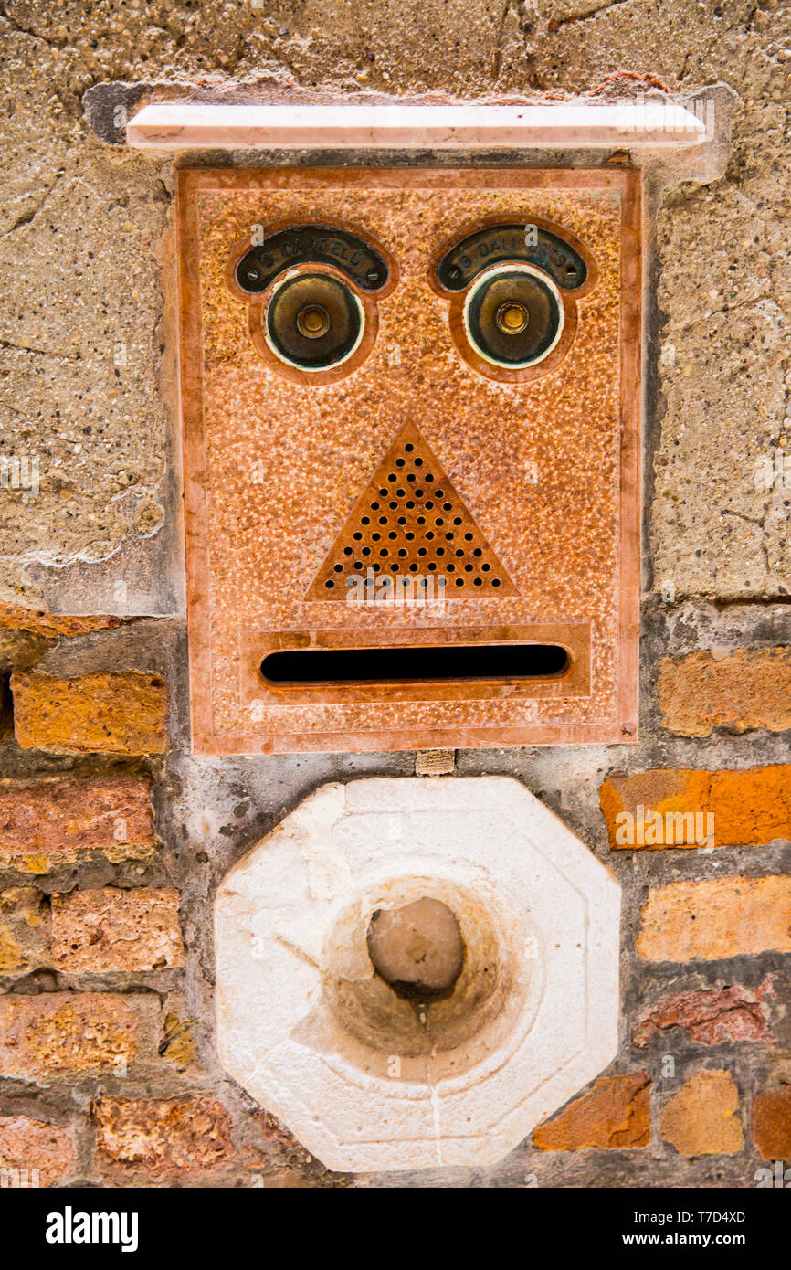 FUNNY ENTRY PHONE IN VENICE, This is an image of a unique entry phone control panel  in the style of an Emoji face - Stock Image
