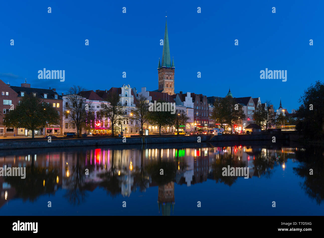 St. Petri Church / Petrikirche and historic houses along the river Trave at dusk at Hanseatic town Lübeck, Schleswig-Holstein, Germany - Stock Image