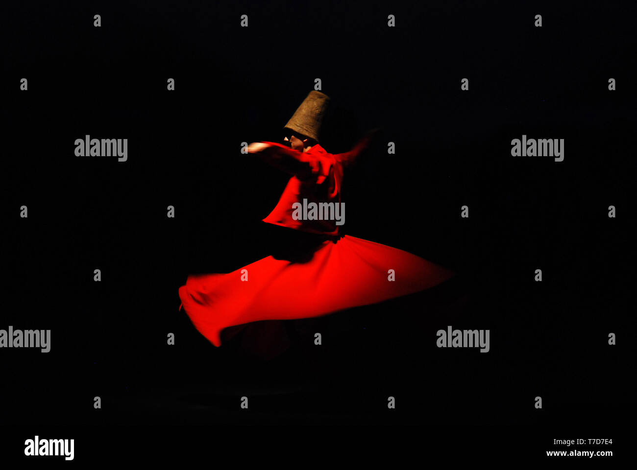 Whirling dervish on black background in red costume - Stock Image