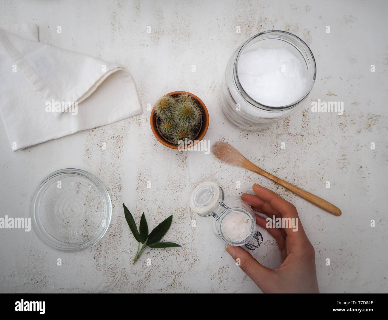 Woman making homemade vegan deodorant with ingredients such as coconut oil and baking soda following a zero waste and plastic free lifestyle Stock Photo