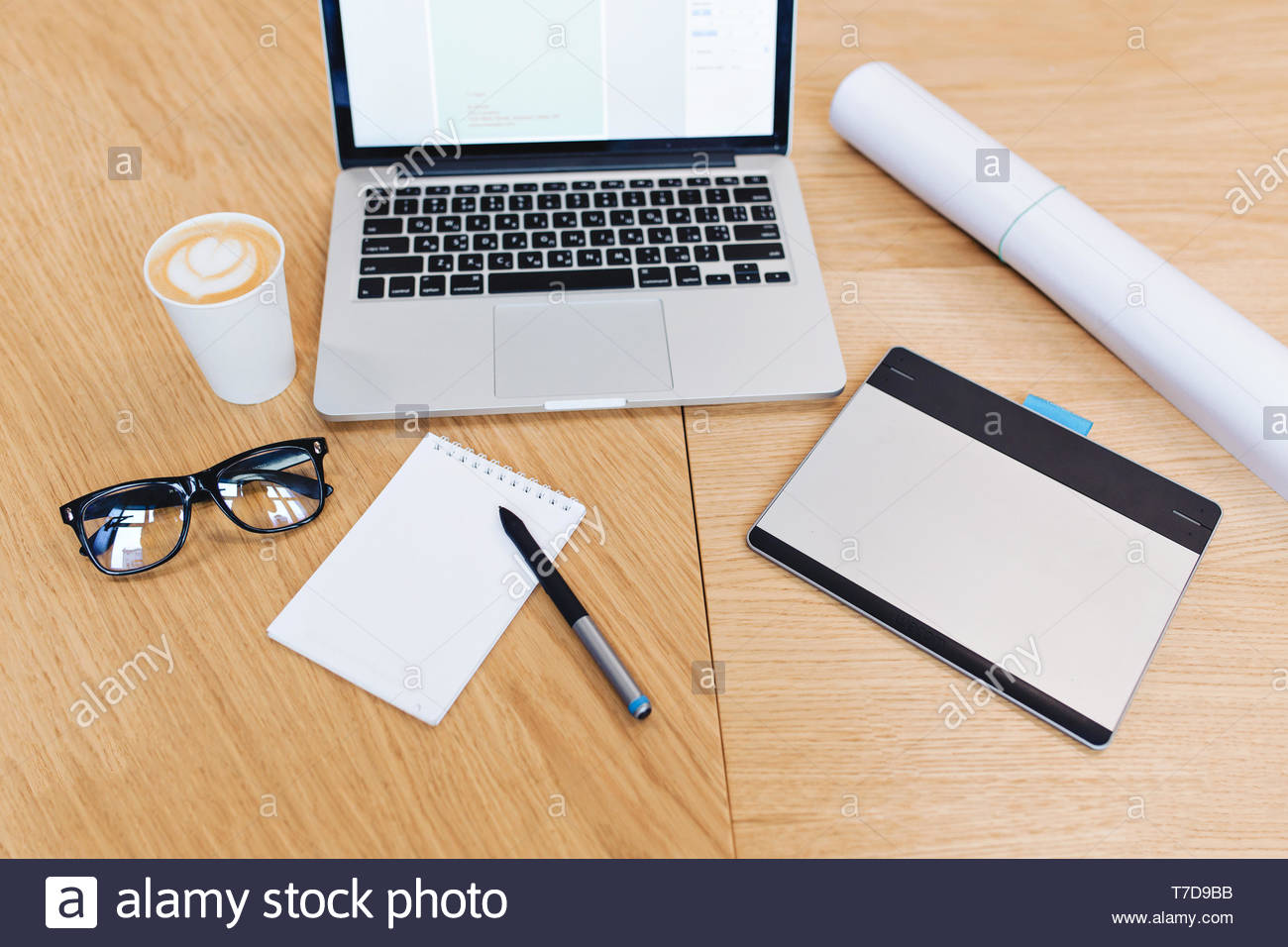 Modern image of work stuff on table from above view. Laptop, black glasses, pencil, notebook, coffee, designing, creativity, working study - Stock Image
