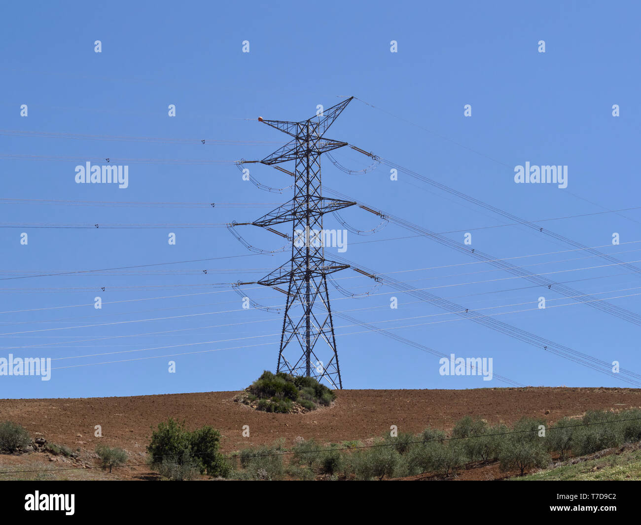 A High Voltage Electricity Transmission Pylon with its suspended overhead Cables on top of a small Hill near Alora in Andalucia in Spain. - Stock Image