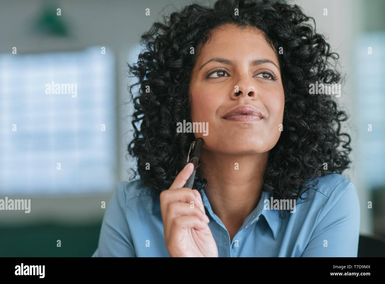 Smiling young businesswoman with a vision for her company - Stock Image