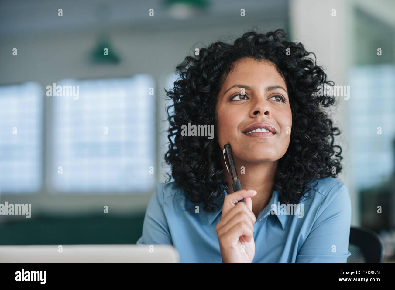 Smiling young businesswoman deep in thought at her office desk - Stock Image