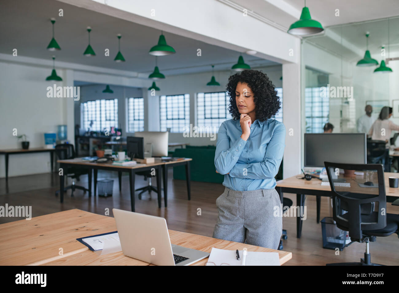 Young businesswoman standing in an office looking deep in thought - Stock Image