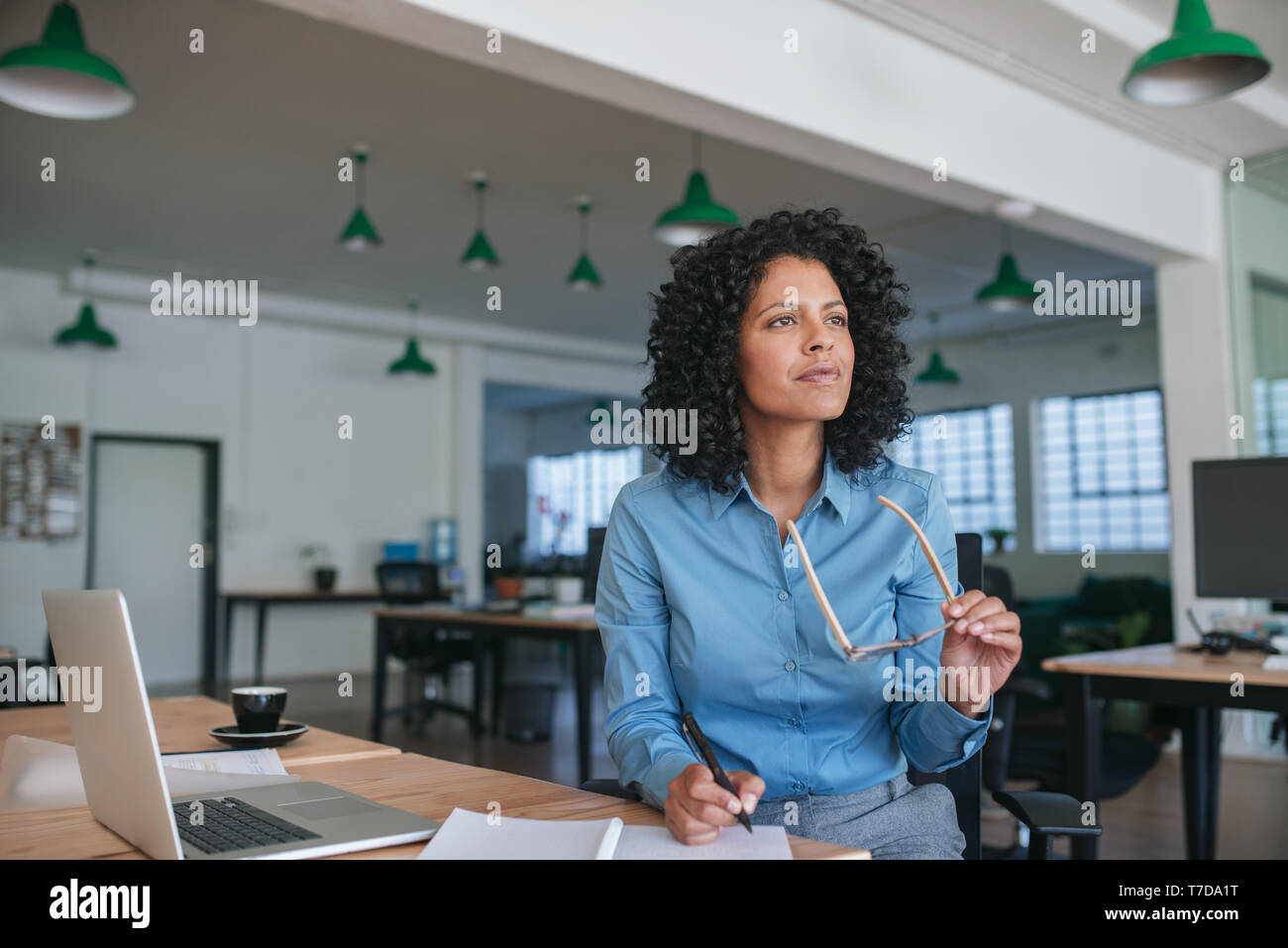 Smiling businesswoman writing ideas in a notebook at her desk - Stock Image