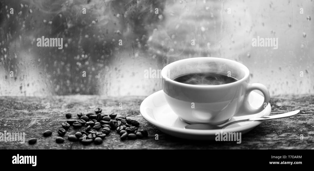 Enjoying coffee on rainy day. Coffee morning ritual. Fresh brewed coffee white mug and beans on windowsill. Wet glass window and cup of hot coffee. Autumn cloudy weather better with caffeine drink. - Stock Image