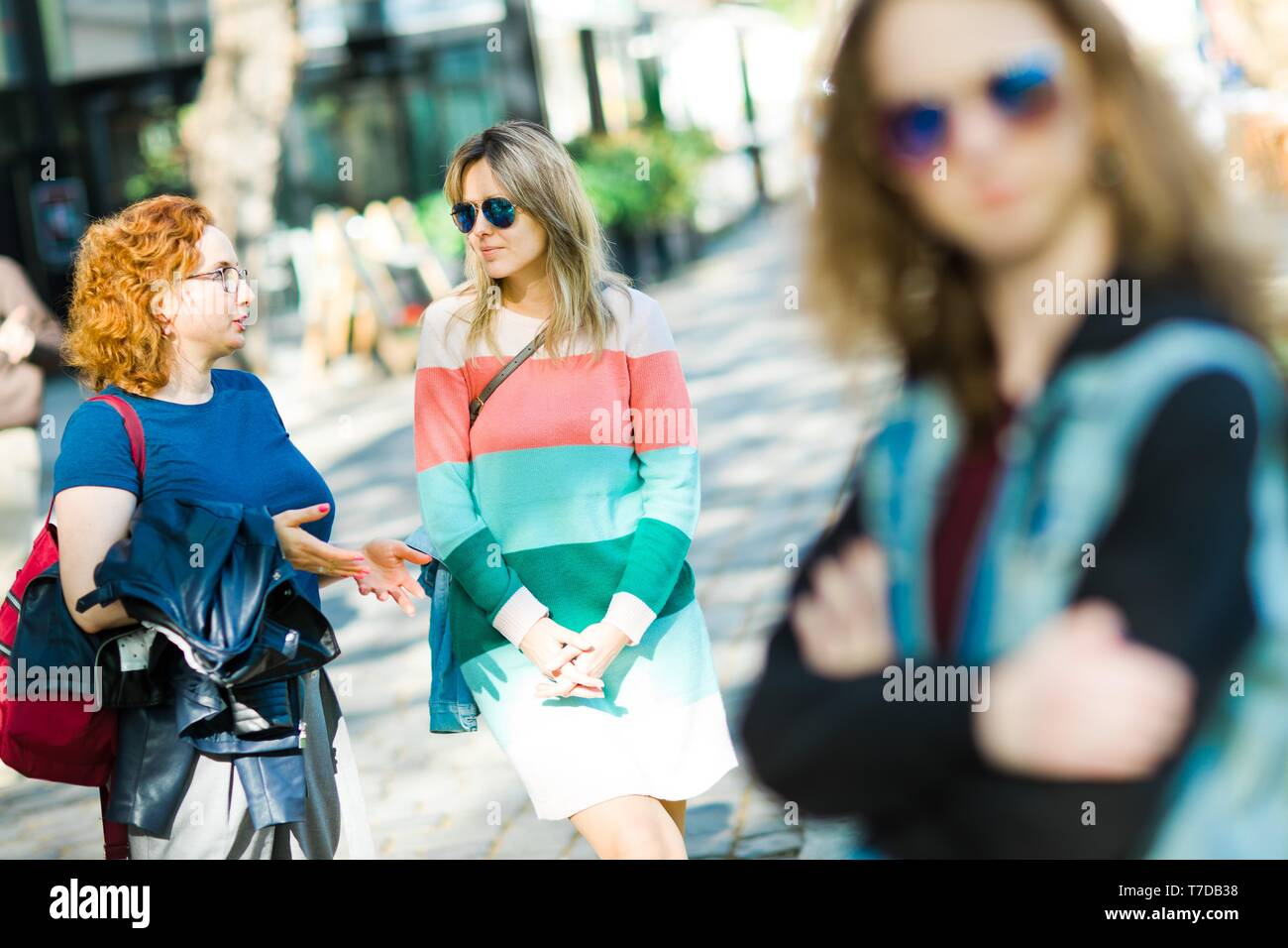 Two women in the city naturally chatting together, bored girl waiting in foreground. - Stock Image
