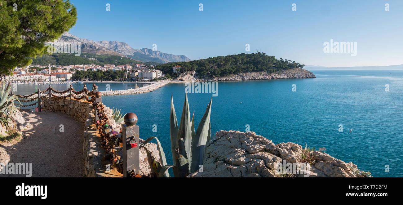 Makarska city port entrance and calm blue sea on sunny summer day - Stock Image