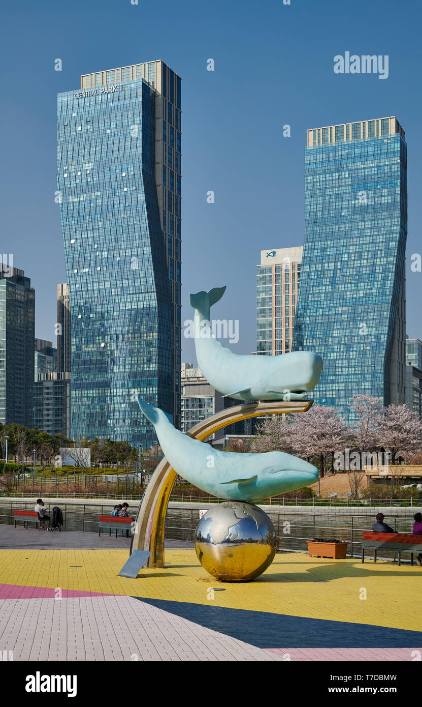 whale figures in Central Park of Songdo International Business District with skyscraper in the back, Incheon City, South Korea - Stock Image