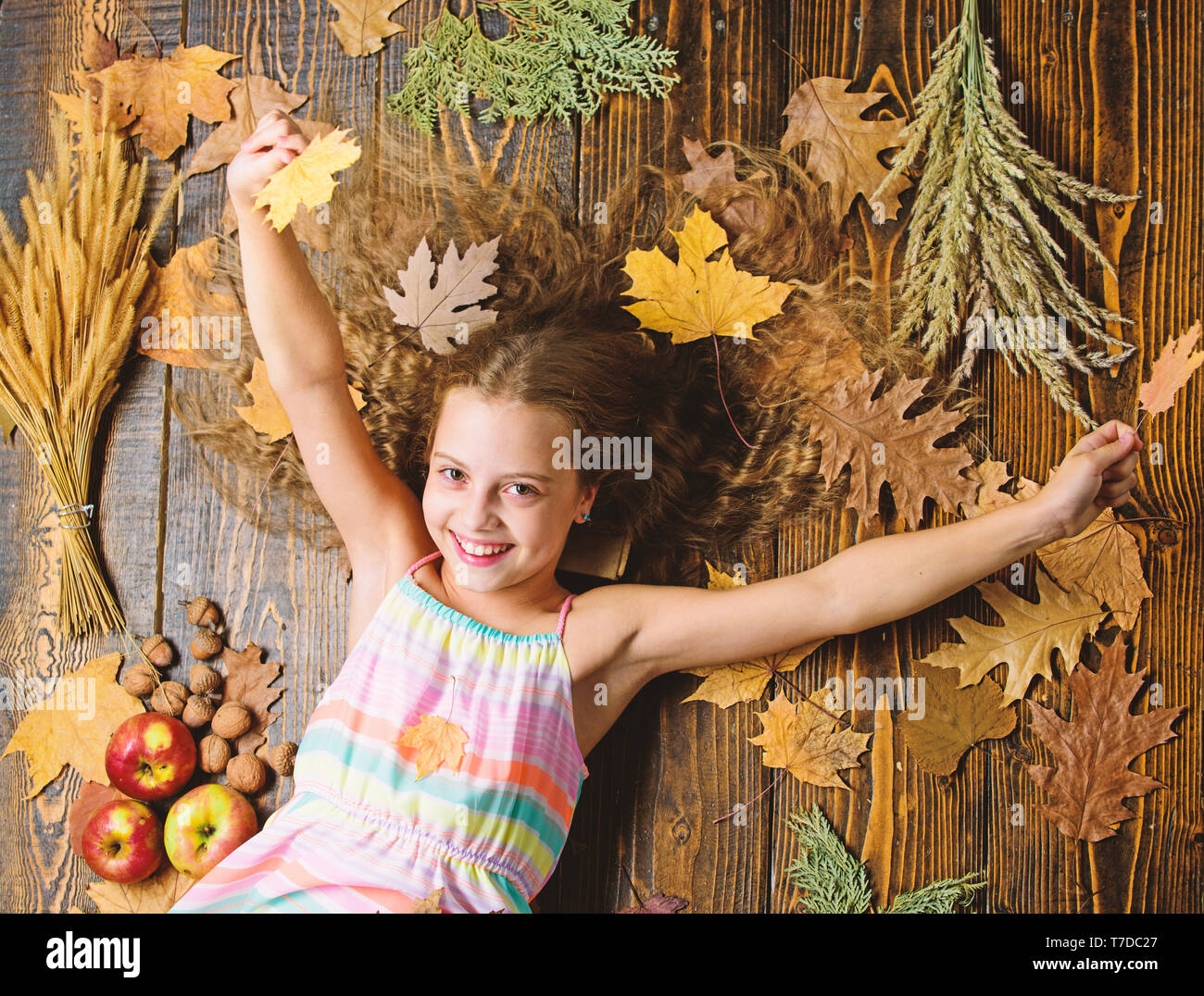 Kid girl smiling face relax wooden background autumn attributes top view child with long hair with autumn maple leaves tips for turning autumn into best