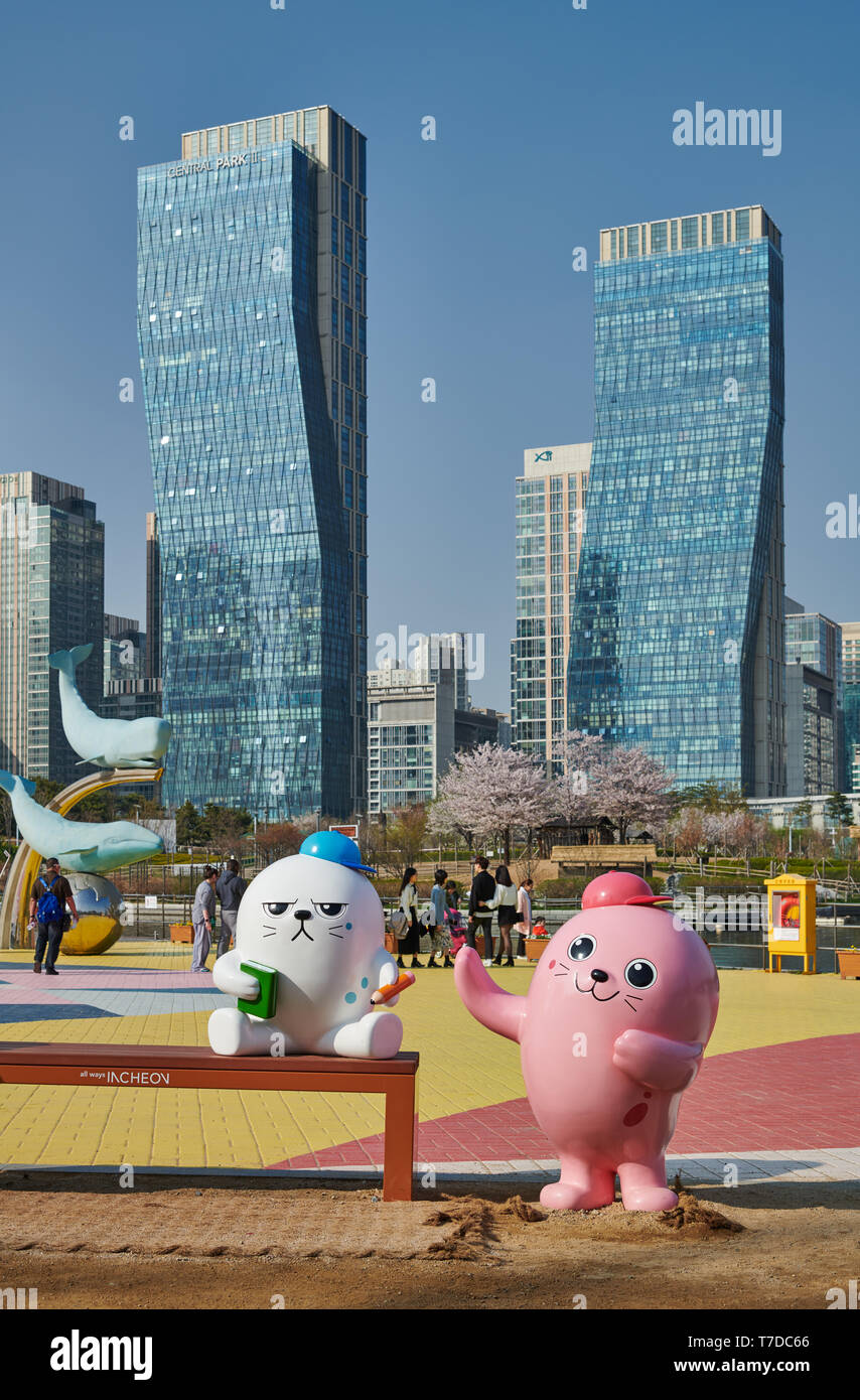 oversized colorful toy figures in Central Park in Songdo International Business District with skyscraper in the back, Incheon City,  South Korea - Stock Image
