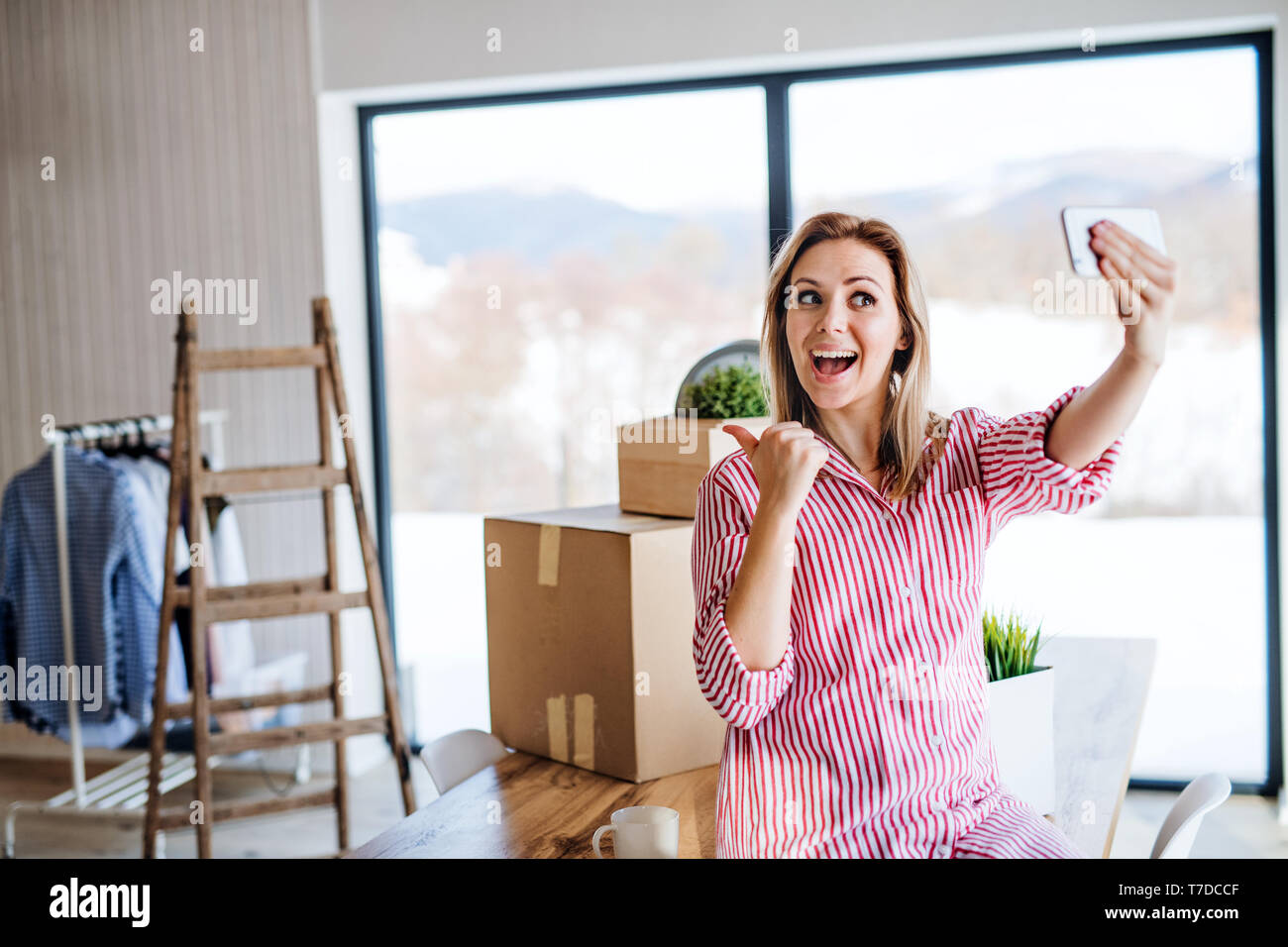 A happy young woman with smartphone moving in new home, grimacing when taking selfie. - Stock Image