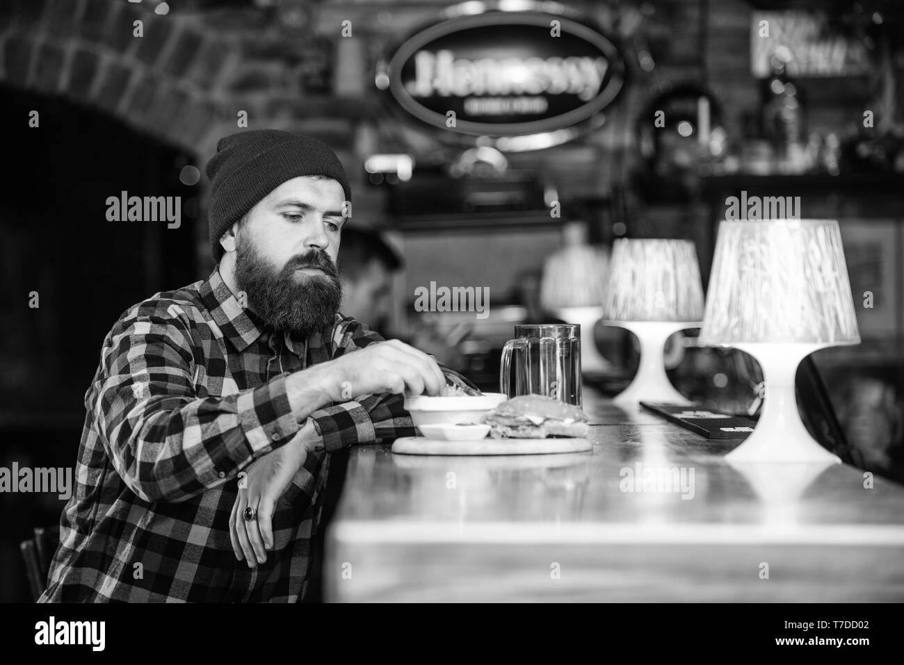Hipster hungry man eat burger. Man with beard eat burger menu. Brutal hipster bearded man sit at bar counter. Cheat meal. High calorie food. Delicious burger concept. Enjoy taste of fresh burger. - Stock Image