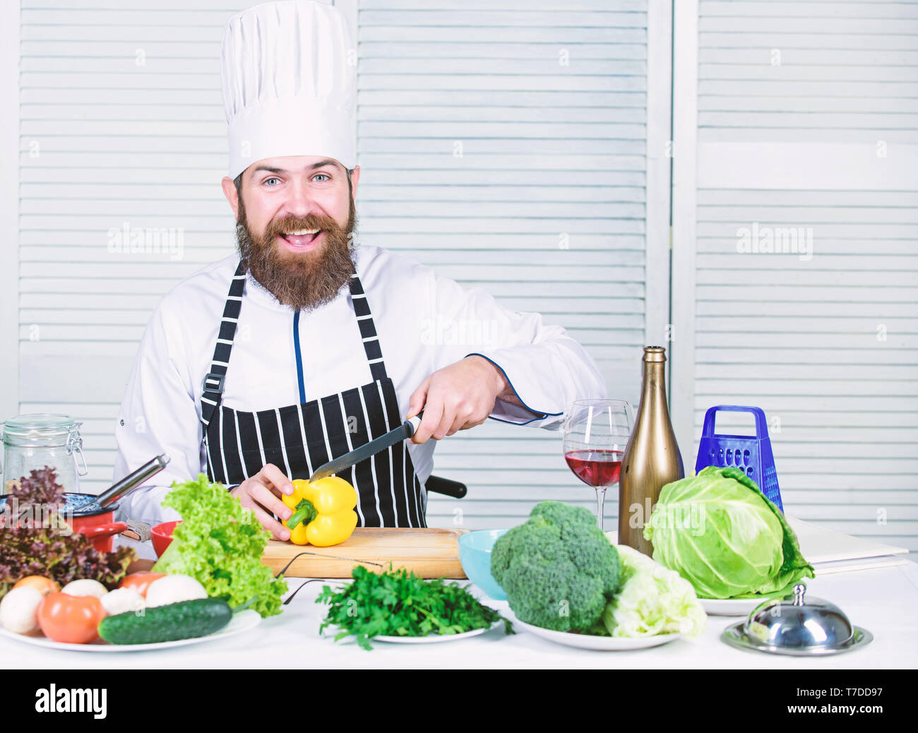 Chop ingredients. According to recipe. Prepare ingredients for cooking. Useful for significant amount of cooking methods. Basic cooking processes. Man master chef or amateur cooking healthy food. - Stock Image