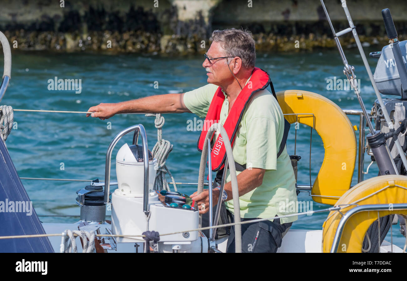 Middle aged man steering a yacht. - Stock Image