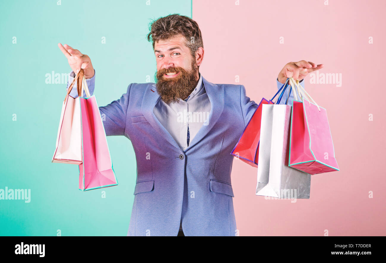 Hipster shopping with discount. Man bearded hipster businessman formal suit carry paper shopping bags. Ready for holiday. Buy gifts for everyone. Buy gifts in advance. Enjoy shopping black friday. - Stock Image