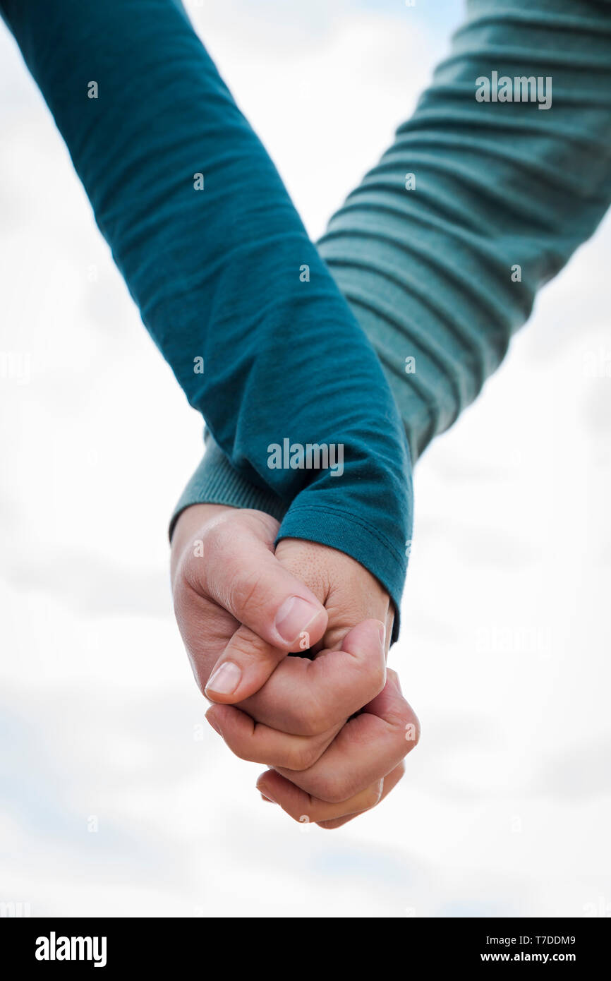 the hands of an intertwined woman and man - Stock Image